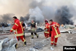 Ратавальнікі нясуць параненага ў выніку выбуху, 4 жніўня 2020 году