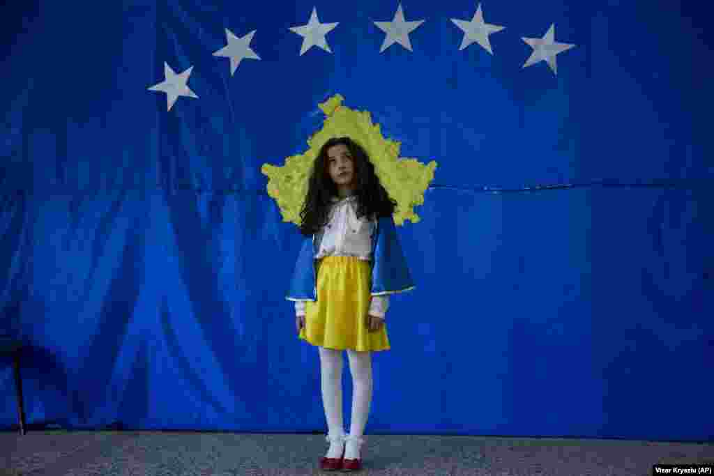 A young girl poses for a photo in front of the flag of Kosovo during an independence celebration ceremony at a school in the village of Sllovi on February 16. (AP/Visar Kryeziu)