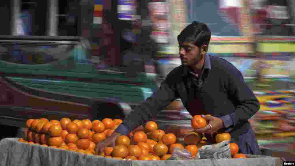 Nawaz, 18, sorts oranges at his roadside stall in Karachi, Pakistan. REUTERS/Akhtar Soomro