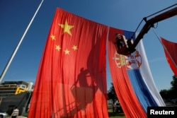 A worker adjusts Chinese and Serbian flags for the upcoming visit of Chinese President Xi Jinping on the site of what used to be China's embassy in Belgrade in June 2016.