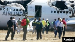 U.S. National Transportation Safety Board investigators work at the scene of the Asiana Airlines Flight 214 crash site at San Francisco International Airport in California on July 7.