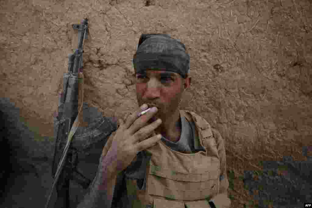 A member of the Iraqi government forces smokes a cigarette as they rest in the village of Al-Khuwayn, south of Mosul, after recapturing it from Islamic State (IS) militants on October 23. (AFP/Ahmad al-Rubaye)