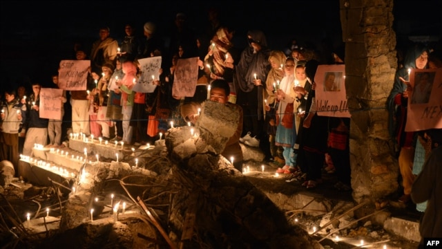 Pakistani Shi'ite Muslims hold candles during a vigil at the site of a bomb attack in Quetta on February 21.