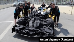 Technicians recover George Russell's car after it struck a loose drain cover and came to a halt on the Baku City Circuit on April 26.