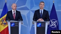 NATO Secretary-General Jens Stoltenberg (right) and Moldovan Prime Minister Pavel Filip give a press conference after their meeting at NATO headquarters in Brussels on March 30.