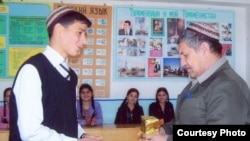 Sazak Durdymuradov (right) receives a present from one of his students in this undated photo