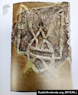 Знайдена в 1908 році в руїнах Десятинної церкви цегла з тризубом князя Володимира. Ілюстрація альбому «Наш герб: українські символи від княжих часів до сьогодення
