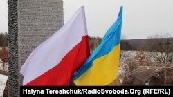 Український та польський прапори на місці поховань поляків у колишній Гуті Пеняцькій, Львівщина, 26 лютого 2017 року