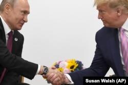 Дональд Трамп и Владимир Путин обмениваются рукопожатием в Осаке. 28 июня2019 года