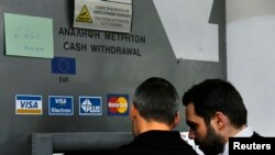 Киприоты снимают деньги в банкомате, объявление на котором сообщает, что максимальная сумма, доступная для снятия в день, составляет 260 евро. Никосия, 22 марта 2012 года.
