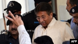 Former Pakistani President Pervez Musharraf is escorted by security personnel as he leaves the Pindi High Court after his hearing in Rawalpindi on April 17.