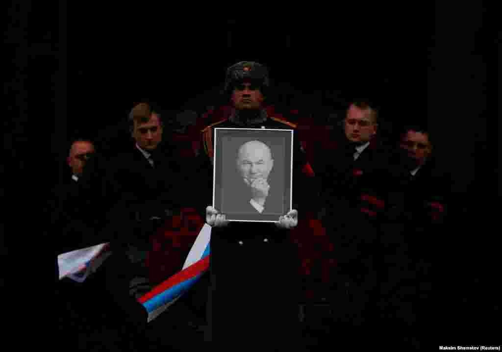 Pallbearers carry the coffin and a portrait of the former mayor of Moscow, Yury Luzhkov, after a memorial service in Moscow on December 12. (Reuters/Maxim Shemetov)
