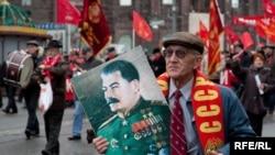 Активист Коммунистической партии держит в руках портрет диктатора Сталина во время марша в честь 92-й годовщины Октябрьской революции. Москва, 7 ноября 2009 года.