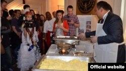 """Посол КР в США и Канаде Мухтар Джумалиев демонстрируют посетителям приготовление кыргызского национального блюда """"Беш-бармак"""". Фото предоставлено посольством КР в США."""