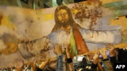 Christians hold a blood-stained portrait of Jesus Christ during a protest in Alexandria on January 2.