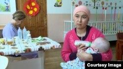 Лора Умарова Аселге сүт берип жатат.