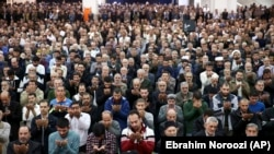 Iranian worshippers attend Friday Prayers in Tehran on January 5. Leading the prayers, hard-line cleric Ahmad Khatami said he backs the government's blocking of social media to disrupt the spread of information about the protests.