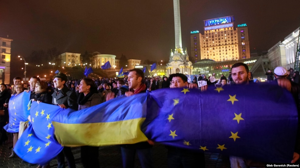 Protesters hold Ukrainian and EU flags during a demonstration to support integrating Ukraine into Europe on November 21, 2013 (Photo Courtesy of Radio Free Europe Radio Liberty)