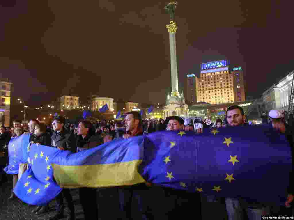 Protesters hold Ukrainian and European Union flags during a rally to support European integration in central Kyiv on November 21, 2013.