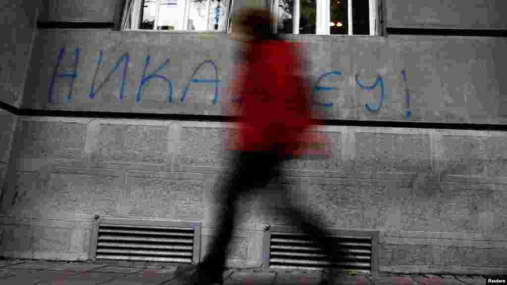 "A man in downtown Belgrade walks past graffiti reading ""Never in the EU"" on December 8. (Photo for Reuters by Marko Djurica)"
