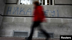 "A man walks past graffiti in the Serbian capital, Belgrade, that reads ""Never in EU."""