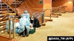 Медики у масках та захисному одязі на одній з палуб круїзного корабля Diamond Princess біля порту Йокогама. За офіціними даними, на борту – 3711 людей (команда і пасажири)