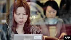 A woman surfs the Internet at a Shanghai cafe.