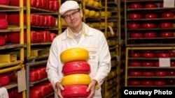 Sergei Chernych displays some of the cheeses his factory has been churning out in sanctions-hit Russia.