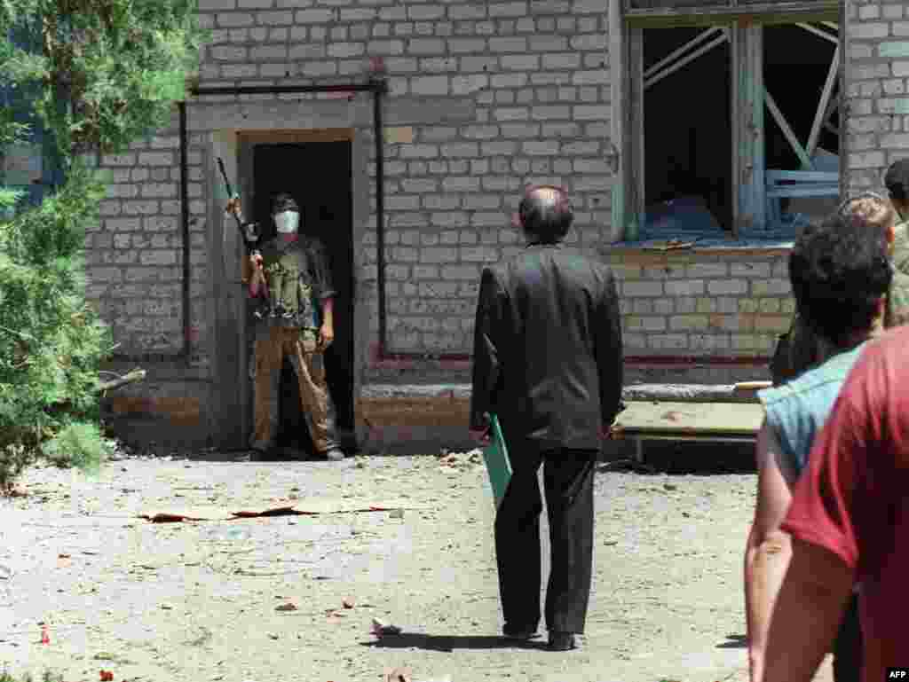 "An unidentified Russian deputy talks with a Chechen fighter at the entrance of the Budennovsk hospital. The Chechen hostage-takers demand an end to the war, and direct talks. Russian President Boris Yeltsin calls the events ""unprecedented in cynicism and cruelty."""