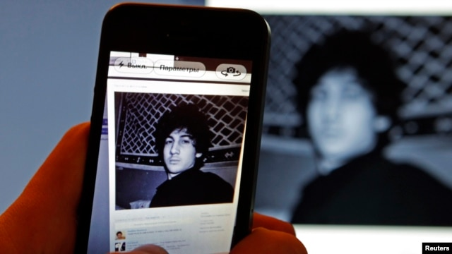 A photograph of Boston Marathon bombing suspect Dzhokhar Tsarnaev on his profile page for the Russian social-networking site Vkontakte (VK), as pictured on a monitor and a mobile phone in St. Petersburg, April 19, 2013.