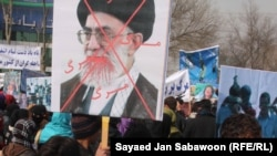 Afghans protesting allegations of Iranian abuse of Afghan refugees hold an image of Iranian Supreme Leader Ali Khamenei at a Kabul demonstration on January 13.