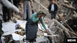 A woman walks among destroyed houses in the Iranian city of Varzaqan in Iran's northwestern province of East Azerbaijan on August 12.