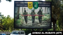 IRAQ -- A picture taken on June 20, 2018 shows a propaganda billboard for the pro-Iran Hezbollah Brigades militia hanging over Palestine Street in the centre of the Iraqi capital Baghdad, depicting three of their masked fighters walking along a road betwe