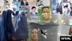 Two Afghan women in Kabul walk past posters of presidential and provincial candidates ahead of elections in 2009.