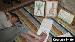 Денис Хасанов показывает, как он рисует ногами. Фото из личного архива семьи Хасановых.
