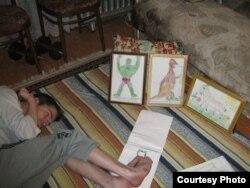 Бала күнінде сал ауруына шалдыққан Денис Хасанов аяғымен сурет салып жатыр. (Сурет Хасановтардың жеке архивінен алынды)