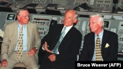 Ніл Армстронґ (ліворуч) разом із командиром «Аполлона-17» Юджином Сернаном (праворуч) слухають члена екіпажу «Аполлона-11» Базза Олдріна