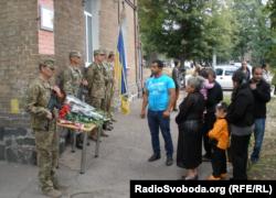 Військові та родина Ігіта Гаспаряна біля будинку з меморіальною дошкою на його честь