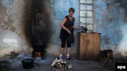 Жена готви надвор на оган, откако во украинскиот град Авдивка беше исклучена струјата по жестоките судири, август 2014 година