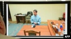 Человек смотрит на монитор с фотографией, показанной по российскому телевидению, на которой запечатлен Райан Кристофер Фогл на допросе в ФСБ.