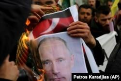 """Курдский демонстрант сжигает фото Путина 24 января 2018 г. За что? Вероятно, за """"защиту границ России"""" в Сирии"""