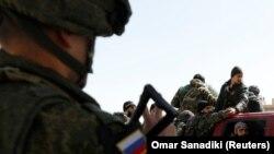 Российский солдат на КПП вблизи Дамаска указывает сирийским войскам направление движения, 2 марта 2018