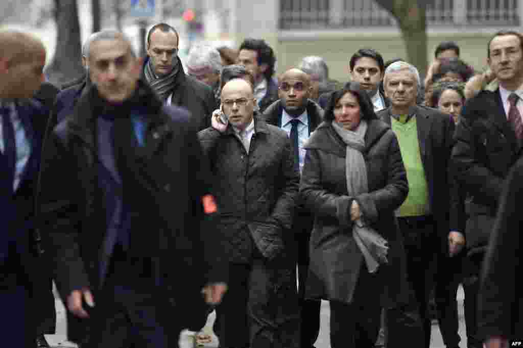 French Interior Minister Bernard Cazeneuve (center left) and Paris Mayor Anne Hidalgo (center right) arrive at the Charlie Hebdo headquarters.