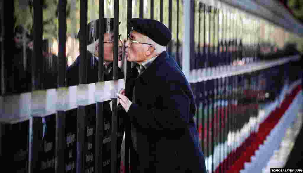 A man kisses a tombstone at the Alley of Martyrs, a cemetery and memorial dedicated to those killed by Soviet troops during the 1990 Black January crackdown, in Baku. Azerbaijan marked the 29th anniversary of the Black January crackdown of the Azerbaijani independence movement in Baku by the Soviet Army in 1990. (AFP/Tofik Babayev)