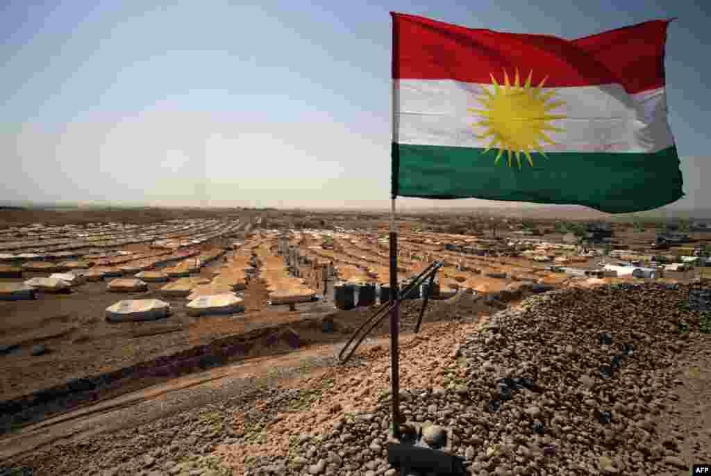 A picture taken on August 29 shows the Kurdish flag waving in the wind above a Syrian refugee camp in Quru Gusik, 20 kilometers east of Irbil, the capital of the autonomous Kurdish region of northern Iraq. (AFP/Safin Hamed)