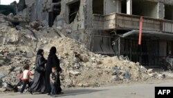 Жінки йдуть повз зруйновану лікарню в сирійському місті Алеппо, 21 квітня 2013 року