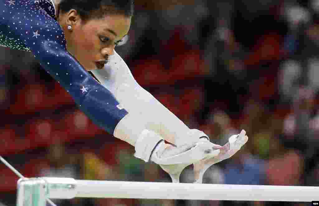 U.S. gymnast Gabrielle Douglas competes on the uneven bars, as the United States won the gold medal in the women's team final.