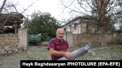 NAGORNO KARABAKH -- A local man carries part of a shell in the city of Martuni, 28 September 2020.