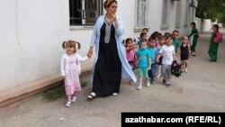 Türkmenistandaky çagalar baglarynyň birinde terbiýeçi zenan we çagalar