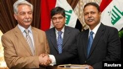 مدير العقود والإجازات في وزارة النفط العراقية عبد المهدي العميدي (يسار) يصافح مدير تطوير الأعمال في شركة النفط الباكستانية عبد الواحد، في مراسم توقيع عقد بين الجانبين ببغداد في 15 تموز 2012.